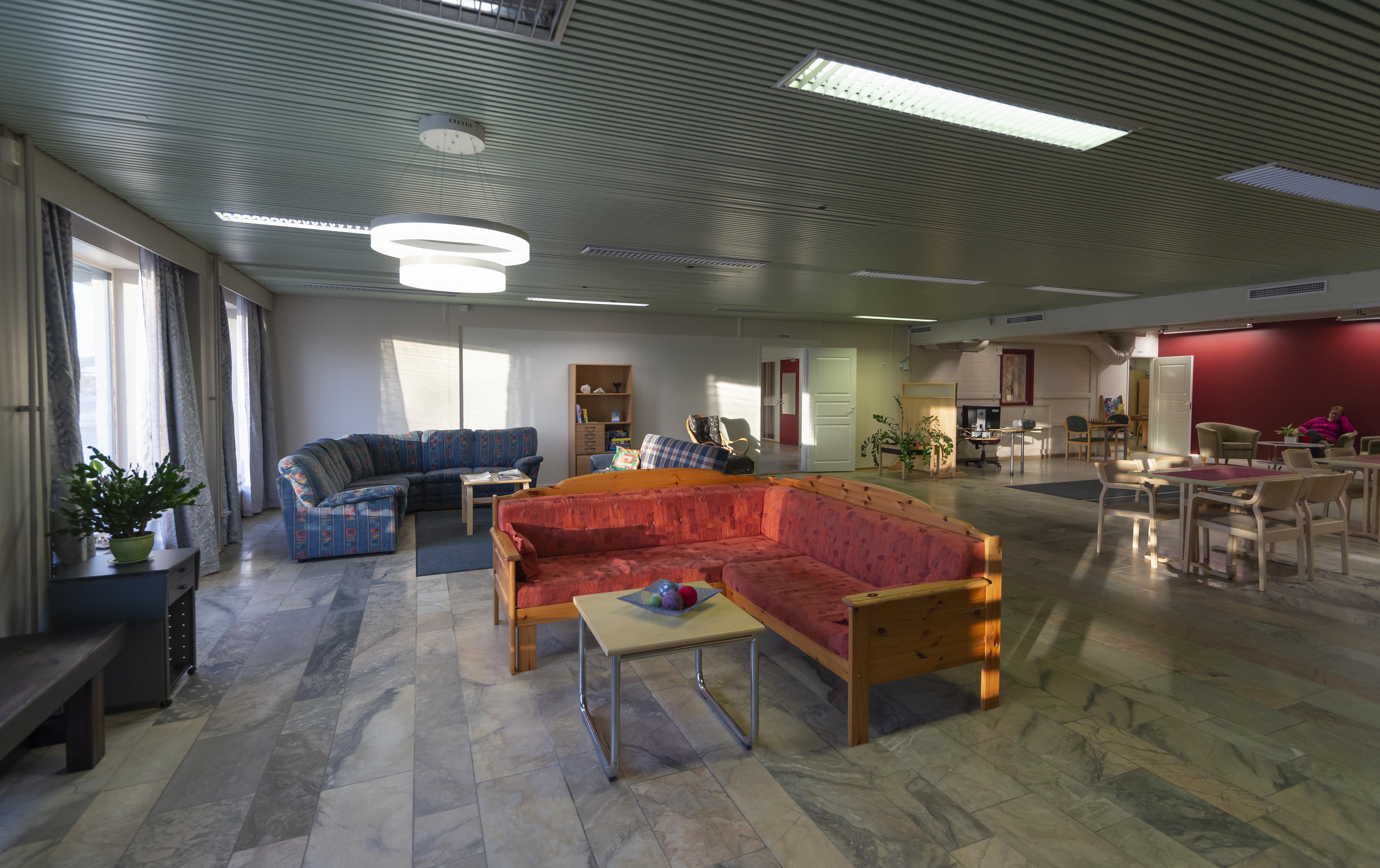 Kuva Osallisuuskeskus Ainolan Olohuone-tilasta. Etualalla punainen sohva ja sohvapöytä. Taka-alalla sininen sohvaryhmä sekä pöytiä ja penkkejä.