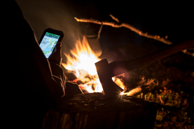 A man looking at an electronic map by the fire