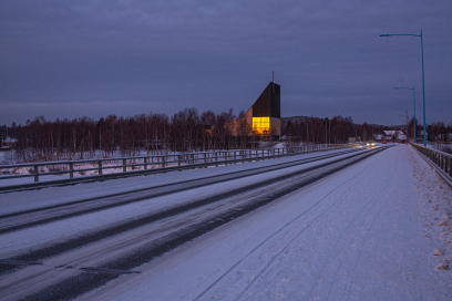 Ivalo church with warm yellow light in winter twilight
