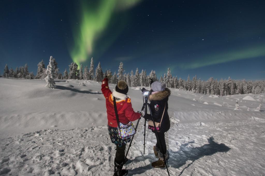 Matkailijat katsomassa revontulia täyden kuun aikana. Kuvassa kaksi naista kameran kanssa. Kuva: jouni männistö