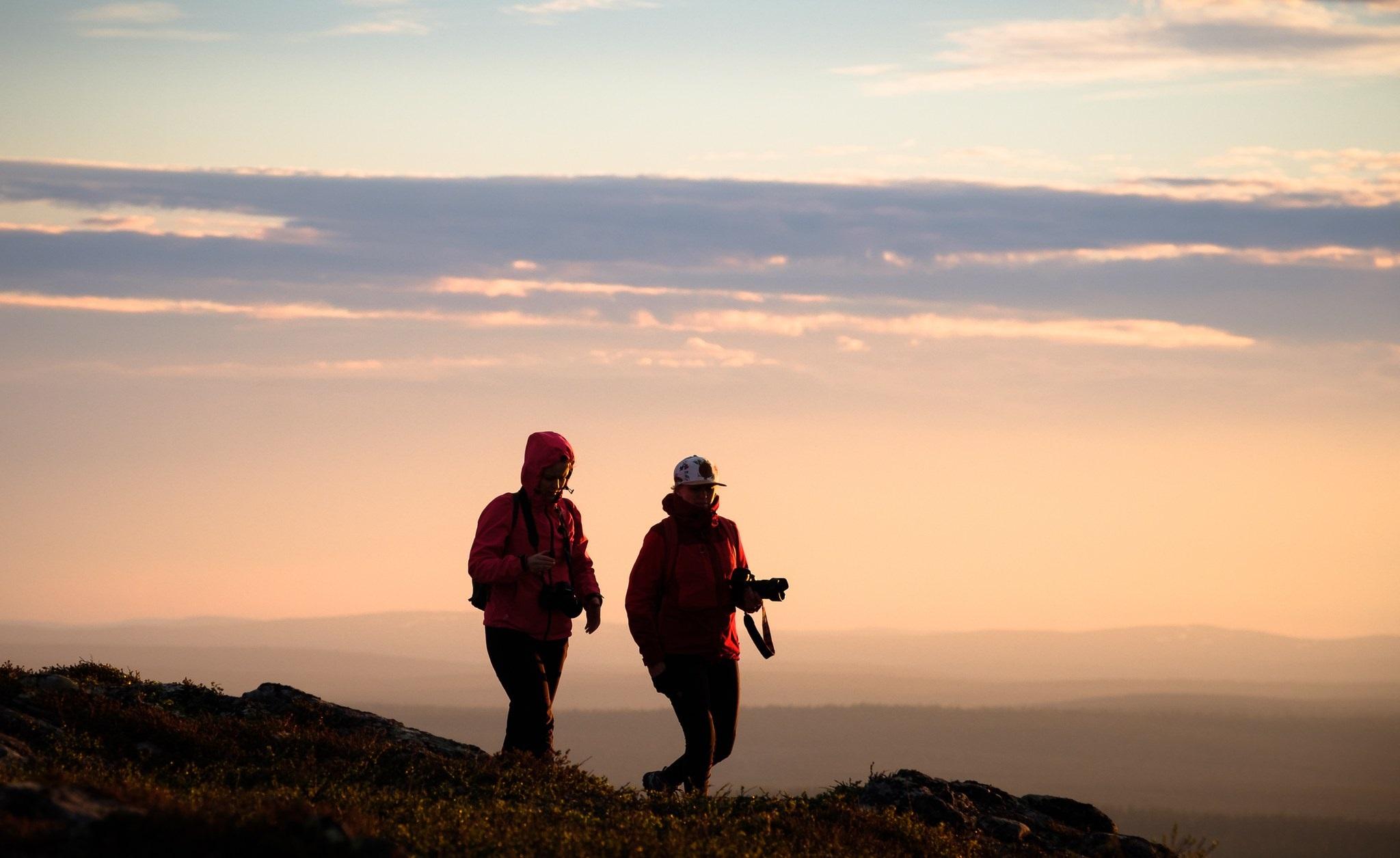 Kuvassa on kaksi valokuvaajaa keskiyön auringossa Kiilpäällä. Kuvaaja Juha Kauppinen