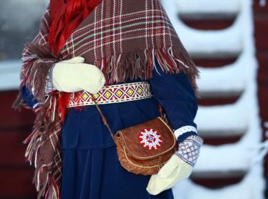 Kuvassa kolttasaamelainen nainen. Asuna perinteisiä asusteita. Kuva: Tanja Sanila