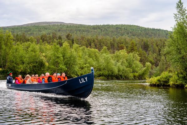 Kuvssa on jokivenematka Lemmenjoella. Veneen kyydissä on kuski ja noin 12 henkilöä. Taustalla tuntureita ja metsää.
